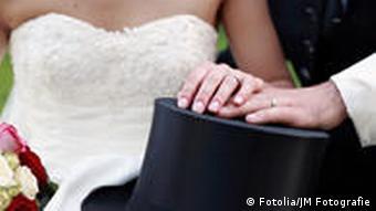 Ein Brautpaar mit den Händen auf einem Zylinder