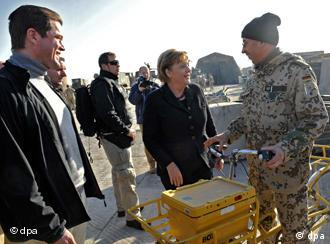 Angela Merkel talks to a soldier on a bicycle