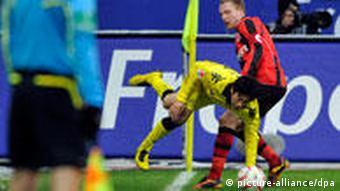 Ein Fußballspieler fliegt über das Knie eines anderen Spielers, der gegen den Fußball treten will