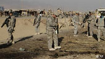 US soldiers inspect the site of suicide attack in Kandahar, Afghanistan, Saturday, Dec. 18, 2010. A suicide bomber attacked an armored car carrying a district chief in the southern Afghan city of Kandahar, killing himself and one civilian bystander, Afghan authorities said. (AP Photo/Allauddin Khan)