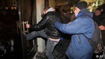 Сотрудник спецслужб заталкивает участника акции протеста в автозак