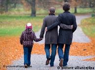 Родина - два чоловіки і хлопчик - на прогулянці у парку