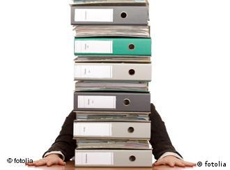 A person behind a stack of folders