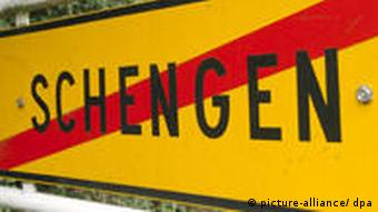 A road sign with the name Schengenwritten in black on yellow, with a red line crossed through it.