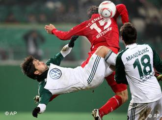 Wolfsburg's Diego Ribas da Cunha, left, and Mario Mandzukic battle for possession against Cottbus's Alexander Bittroff