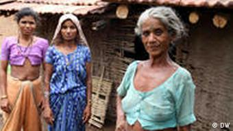 Three women in front of a typical mud farm house in South Gujarat