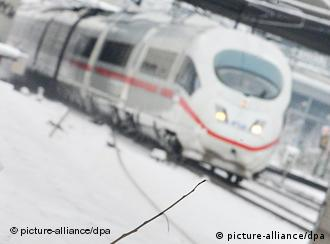 A Deutsche Bahn train travels through snowy tracks