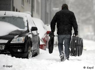A man carrying a suitcase on a snowed-in street