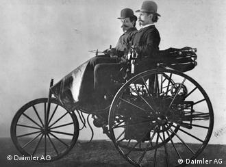 Carl Benz (right) in his patented vehicle