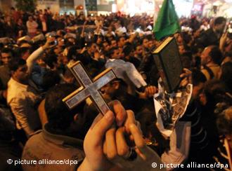 Egyptian Muslims and Christians raise the Koran and Cross