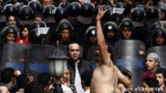 An Egyptian Christian protests in front of security forces
