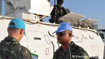 Zwei Soldaten der UNO-Mission vor einem weißen UN-Panzer in Port-au-Prince (Foto: AP)