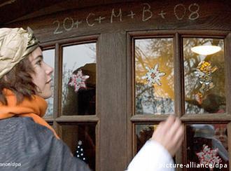Sternsingerin Luisa Lange schreibt am Sonntag (06.01.2008) den Segenswunsch 20+C+M+B+08 an die Tür eines Hauses in Belm (Landkreis Osnabrück). Auch in diesem Jahr zum Dreikönigsfest ziehen Sternsinger in Verkleidung der Heiligen Drei Könige Caspar, Melchior und Balthasar von Haus zu Haus, singen Lieder oder sagen Gedichte auf und sammeln dabei für karitative Zwecke. Foto: Friso Gentsch dpa/lni +++(c) dpa - Bildfunk+++