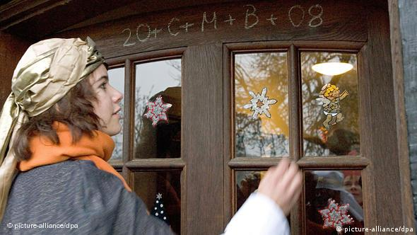 Sternsinger Luisa Lange writes the traditional blessing on the door of a house in Belm