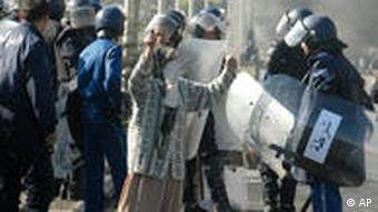 Eine verschleierte Frau skandiert vor einem algerischen Polizisten (Foto: AP)