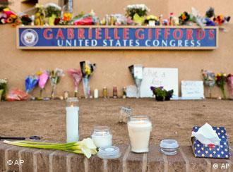 Candles and flowers are placed outside the office of US Rep. Gabrielle Giffords, in Tucson, Arizona