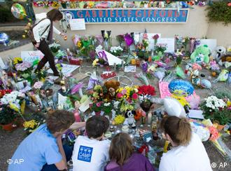 Well-wishers pay their respects at a makeshift memorial outside US Rep. Gabrielle Giffords' office in Tucson, Arizona