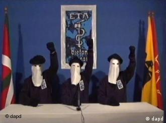 Masked ETA members raise their fists