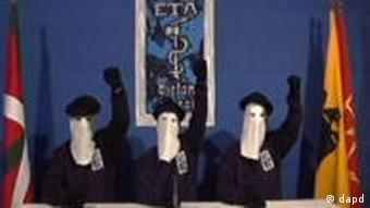 3 ETA members, masked and with arms upraised, before logo and flanked by flags