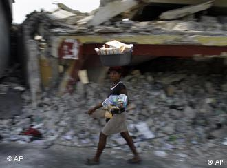 Woman walking past wrecked house in Haiti