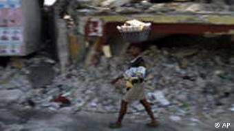Haitian woman walks past house destroyed by earthquake