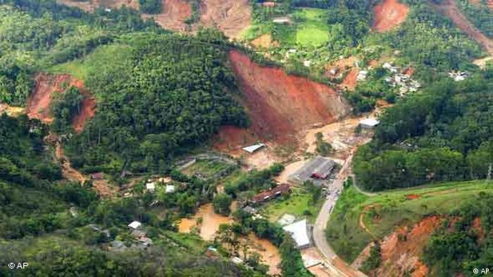 Foto aérea mostra área morro onde houve deslizamento. Área está sem árvores, apenas com terra. Na outra parte do morro, que não deslizou, podem ser vistas muitas árvores