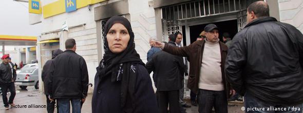 تجمع مردم در مقابل بانکی در تونس که به آتش کشیده شده است