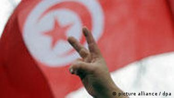 A Tunisian flag and hand making a victory sign, a symbol of the revolution