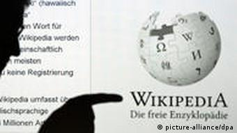 The silhouette of a man points at a screenshot of Wikipedia