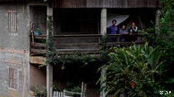 People stand on the porch of their home at the edge of landslide damage in the Caleme neighborhood in Teresopolis, Brazil, Thursday, Jan. 13, 2011.