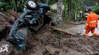A rescue worker walks among debris after landslides at Caleme neighborhood in Teresopolis, Brazil, Thursday, Jan. 13, 2011.
