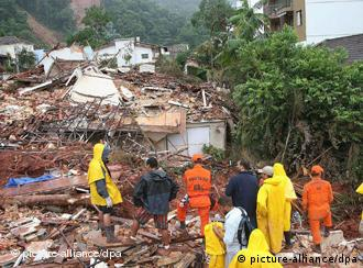 Cars sit in debris in a flooded street in Teresopolis, Rio de Janeiro state, Brazil, Wednesday Jan. 12, 2011.