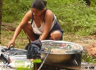 A woman washes clothes in a water bucket