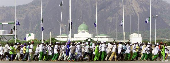 Supporters of leading opposition leader Muhammadu Buhari of the All Nigeria People's Party (ANPP), run against a backdrop of the Legislature and Aso Rock at a party rally in the Nigerian capital Abuja Tuesday, April 8, 2003. The rally in support of Buhari and his running mate Chuba Okadigbo was held ahead of the upcoming general elections to be held on Saturday, April12, 2003 and presidential elections on Saturday, April 19, 2003. (AP Photo/Ben Curtis)