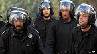 Riot police officers detain a protestor during clashes in Tunis, Friday, Jan. 14, 2011