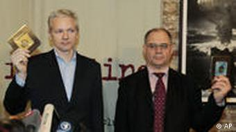 Julian Assange and Rudolf Elmer holding up CDs