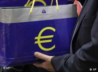 An assistant holds up two bags with a euro symbol during a meeting of eurogroup finance ministers at the EU Council building in Brussels, Monday, Jan. 17, 2011