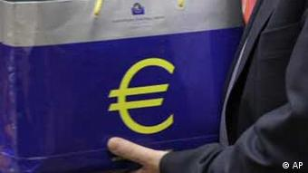 An assistant holds up two bags with a euro symbol during a meeting of eurogroup finance ministers at the EU Council building in Brussels, Monday, Jan. 17, 2011. Finance ministers of the 17 euro countries are locking horns Monday over how to fight their crippling debt crisis amid evidence that the European Central Bank has so far been taking on the burden of calming jittery bond markets. (Foto:Virginia Mayo/AP/dapd)
