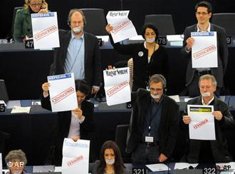 MEPs hold up protest posters in parliament
