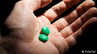 A hand with two green pills