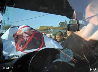A crowd holds a poster with a picture of the minister crossed out in front of her car
