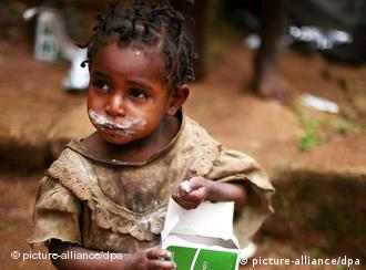 A small girl eating from a food package