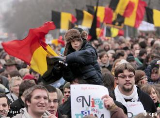 Protesters waving Belgian flags march in the street