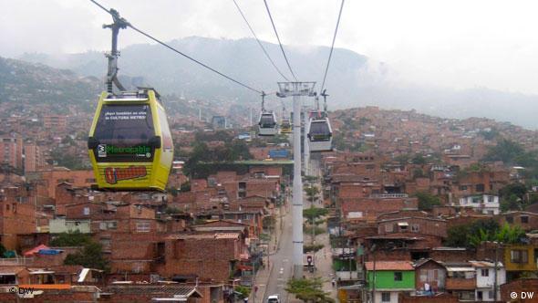 Blick ins Tal in Medellin, viele Häuser, auf der linken Seite eine Gondel der Seilbahn (Foto: DW/Alexa Meyer, Patrick Benning)