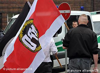 An NPD supporter holding a black-red-white party flag