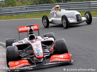 British Formula One driver Lewis Hamilton steers the old Silberpfeil (Silver Arrow)W25 from the year 1934 at the Nürburgring Nordschleife next to his 2009 McLaren Mercedes MP4-24.