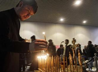 A clergyman lights candles at the site of a blast at Domodedovo airport near Moscow on Wednesday, Jan. 26, 2011. Security was tightened in Moscow on Tuesday, after a suicide bomber set off an explosion that ripped through Moscow's busiest airport on Monday. (Foto:Sergey Ponomarev/AP/dapd)