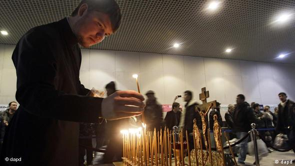 A clergyman lights candles at the site of the blast at Domodedovo airport