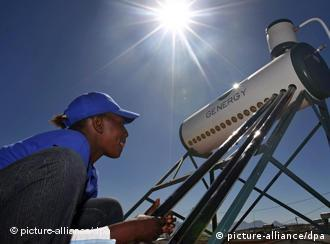 A South African woman installs a solar water heating unit on the roof of a home in Kuyasa outside Cape Town, South Africa, as part of a UN scheme to back clean development