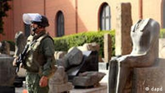 An Egyptian army soldier stands guard near antiquities of the Egyptian museum in Cairo